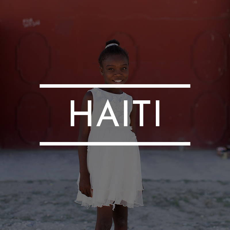 """HAITI"" is written on top of an image of a young Haitian girl wearing white standing against a red gate"