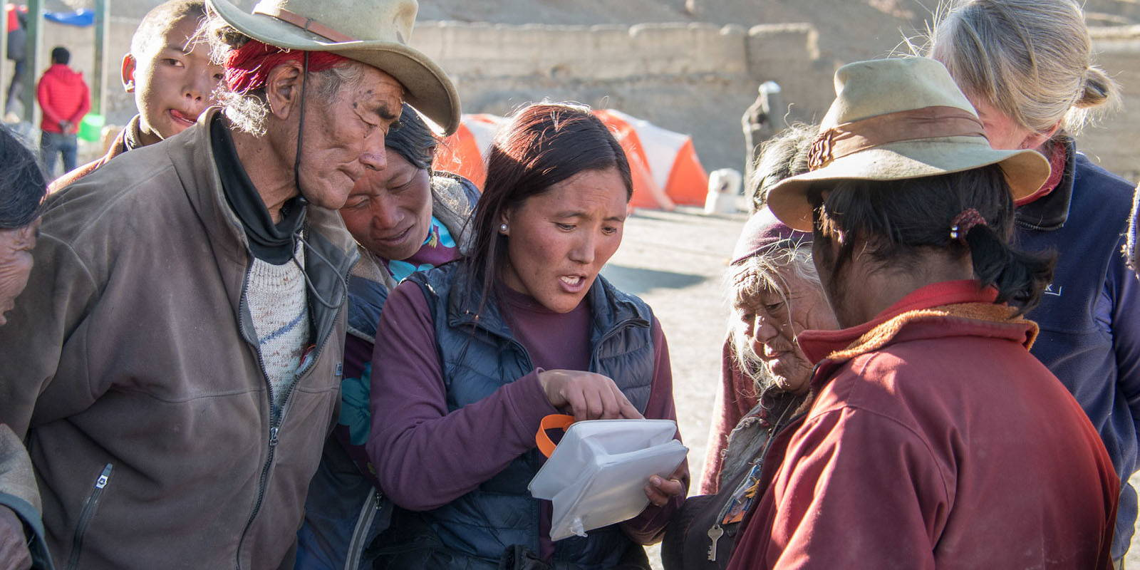 A woman explaining how to use a LuminAID light to a group affected by the Nepal Earthquake.