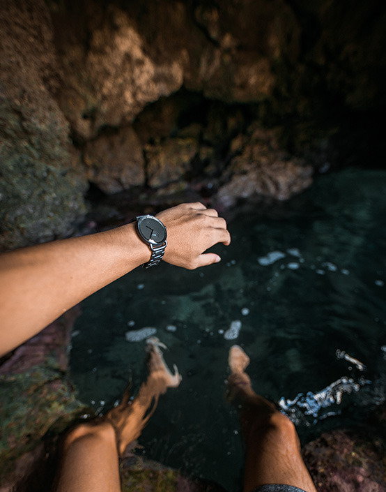 wrist shot of watch in cave by water