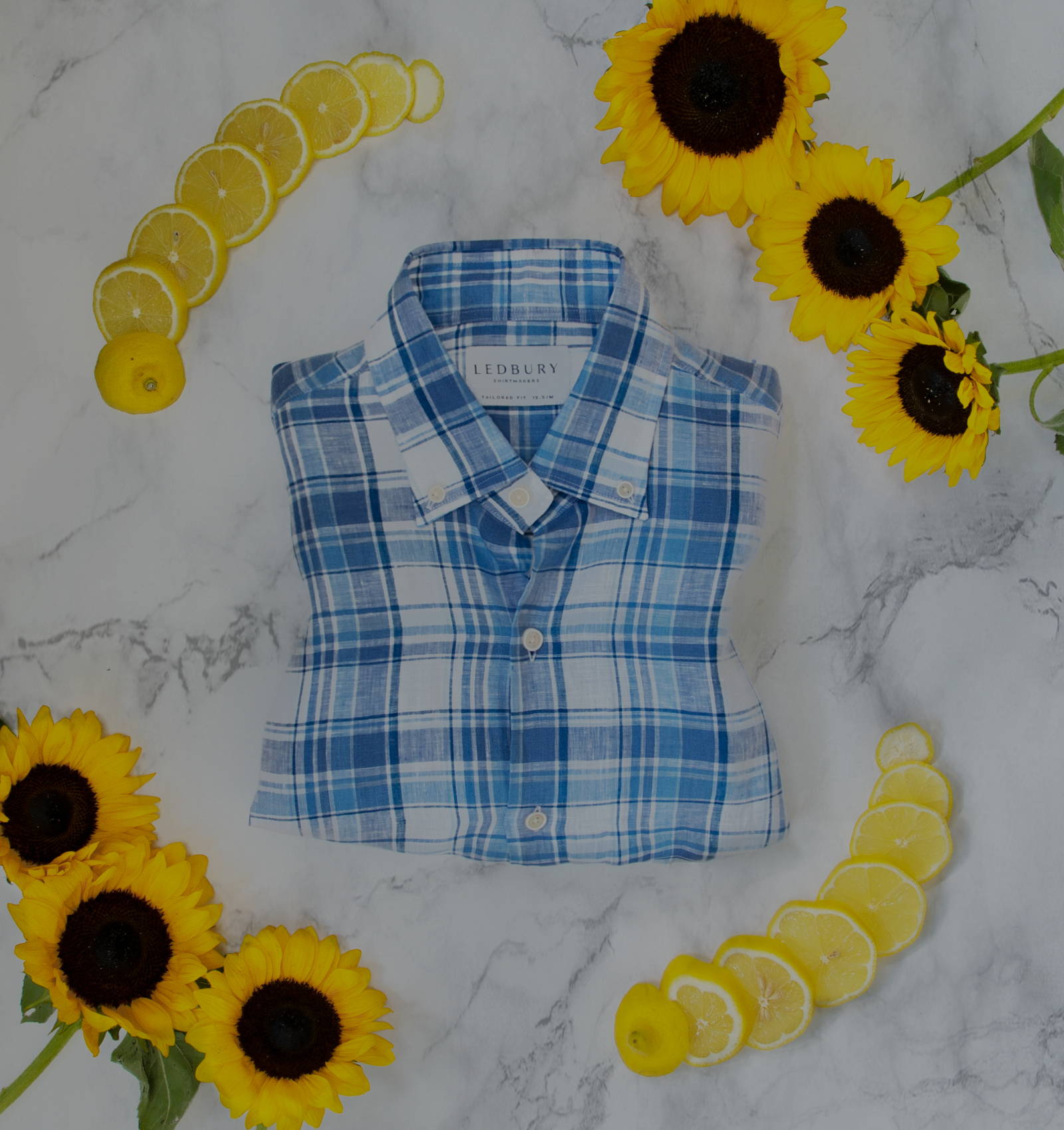 The Blue Raulin Linen Plaid Casual Shirt surrounded by lemons and sunflowers on a marble table.
