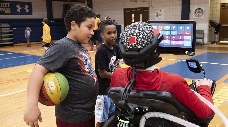 En person som bruker Tobii Dynavox-kommunikasjonsenheten montert på rullestolen.