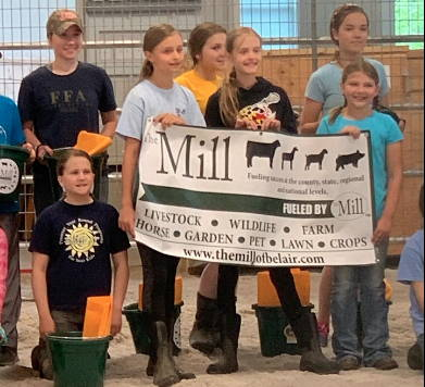 Livestock children holding mill banner