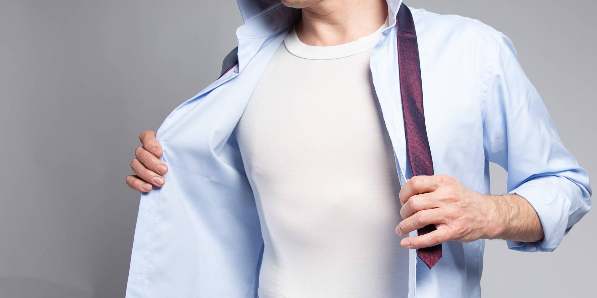 Man wearing white bamboo crew neck undershirt under a blue dress shirt and tie