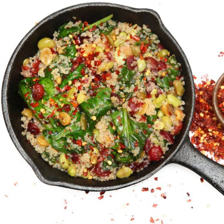 cast iron pan of quinoa spinach and cranberry side dish