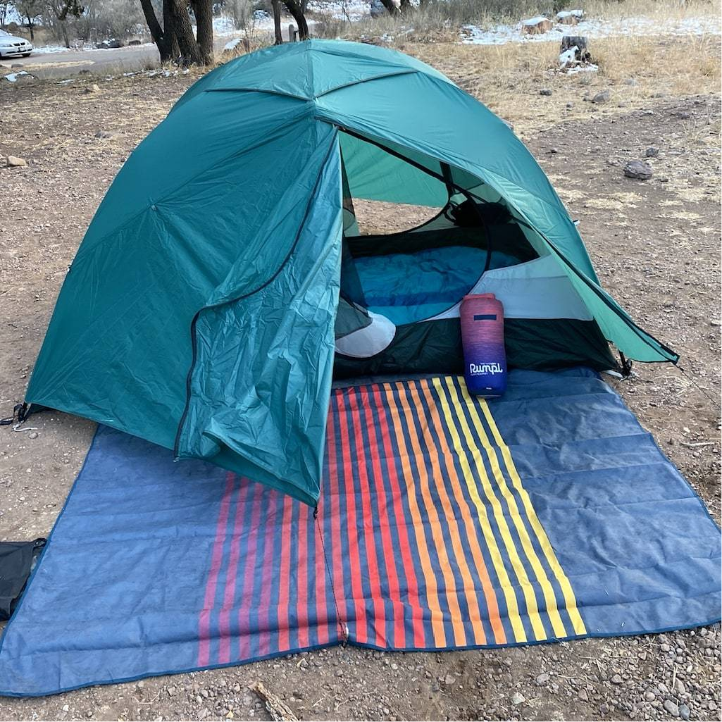 Green tent with blue rumpl stash mat on the ground