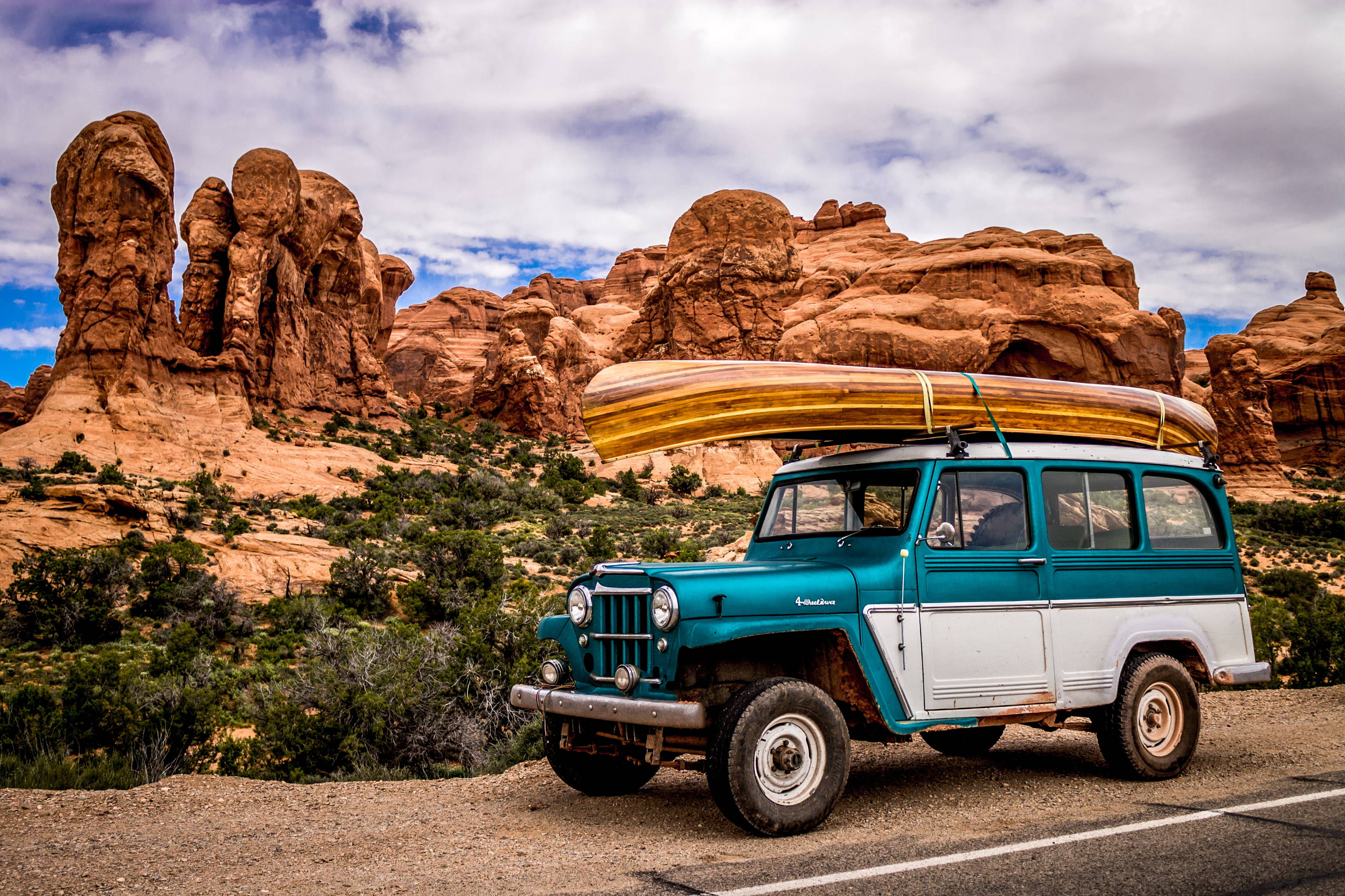 Best National Parks in California & Beyond: Old teal and white SUV with canoe on top sits on side of road in Arches National Park.