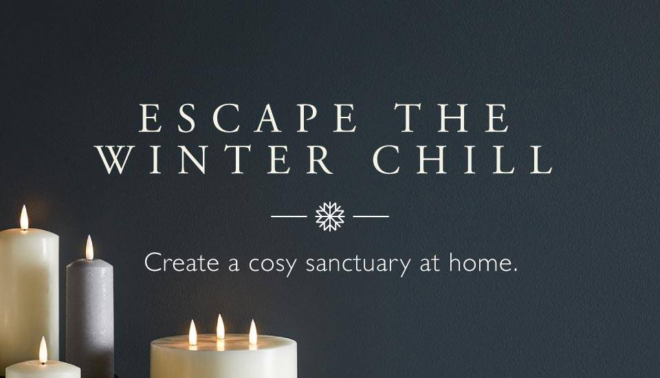 Escape the winter chill - Assortment of TruGlow candles styled on table top with micro lights weaved in between the display on a navy blue background