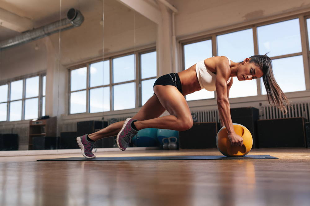 Portrait of a fit and muscular woman doing intense core workout with kettlebell in gym. Female exercising at crossfit gym.|4 benefits of tabata training