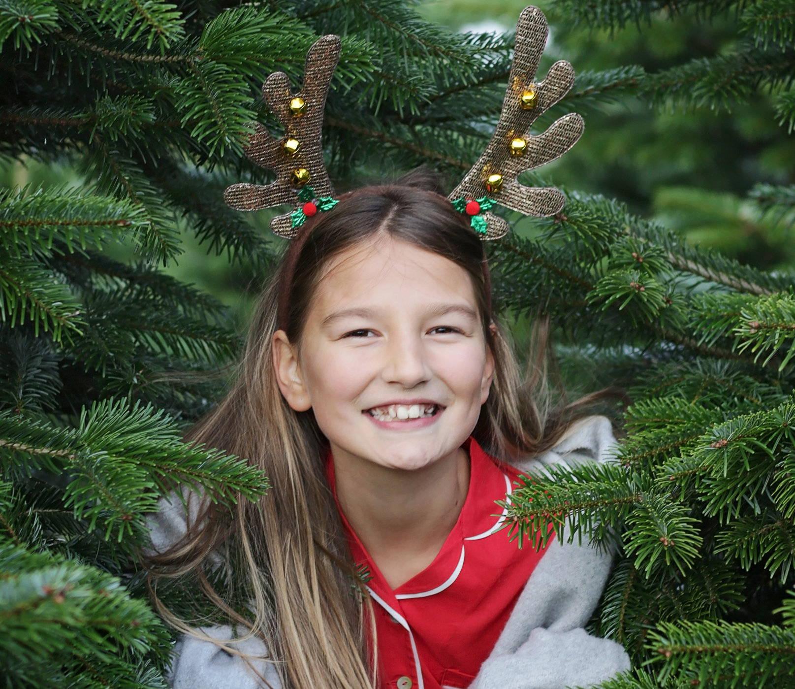 a girl smiling while wearing raindeer horn headband