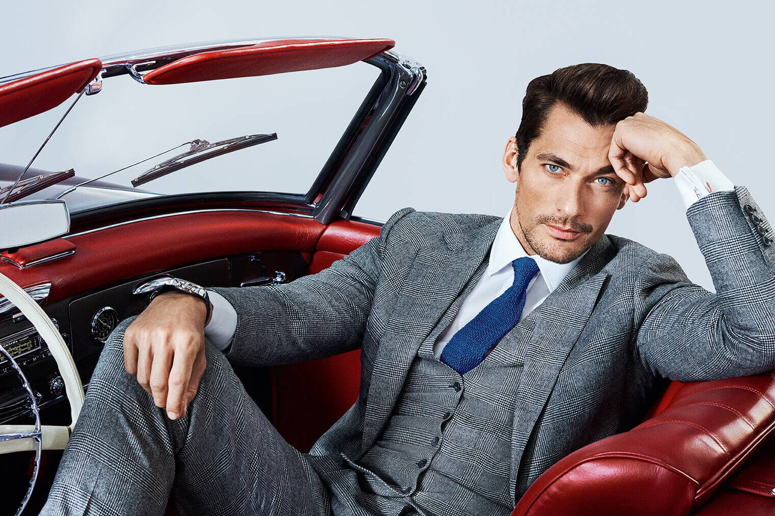 David Gandy Wearing A Grey Suit Sitting In A Red Convertible Car