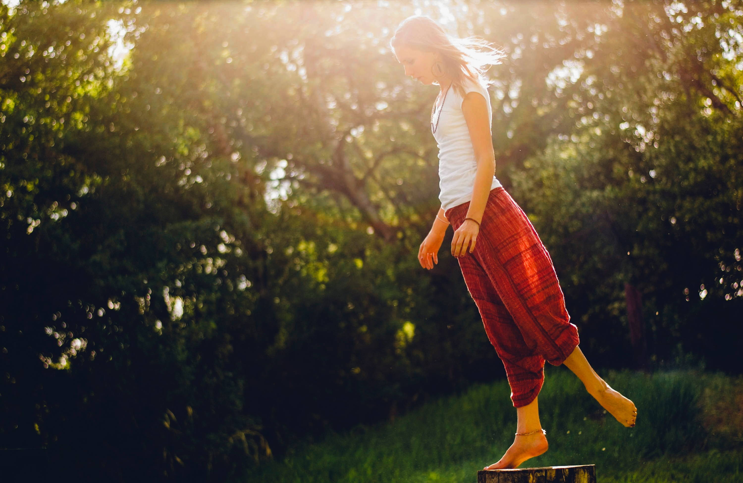 A woman in red hemp pants stands on a tree stump and leans forward.