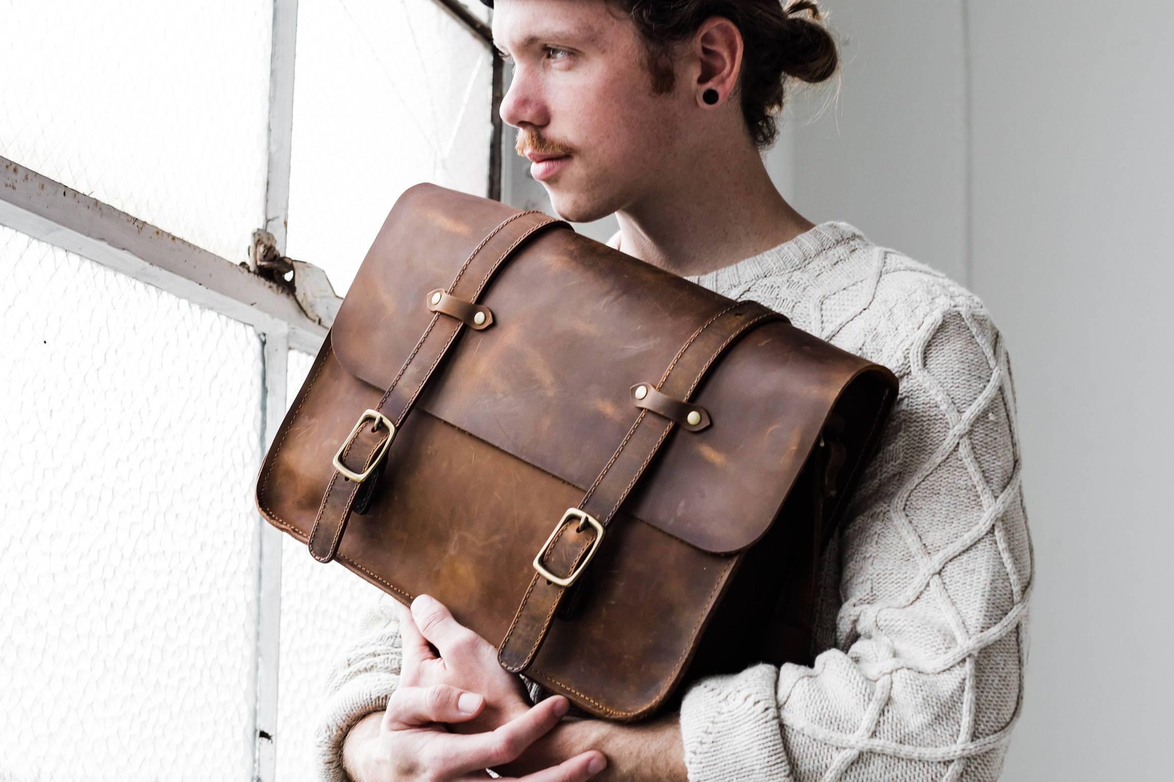 man holding handmade leather attache bag by portland leather goods