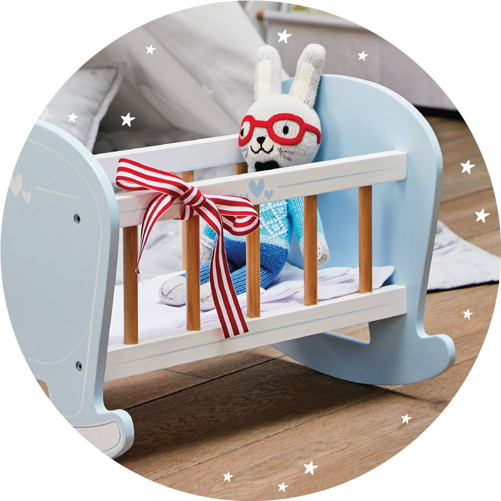 Wooden toy cot with small teddy inside