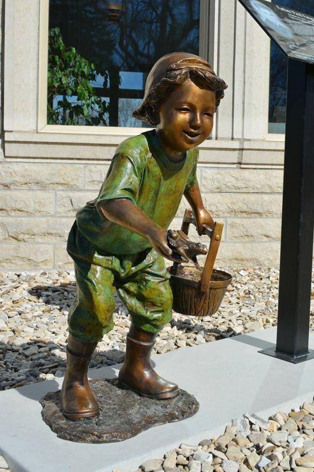 Bronze statue of little boy catching frogs