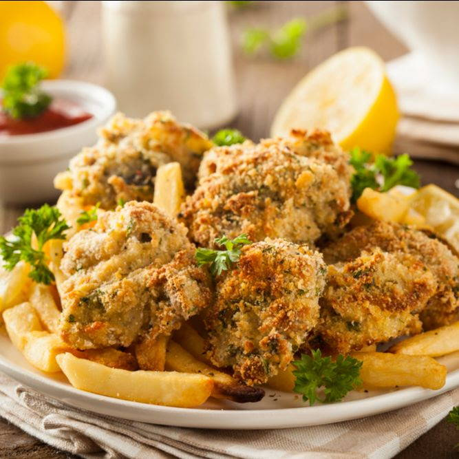 fried oysters with parsley and french fries on a plate