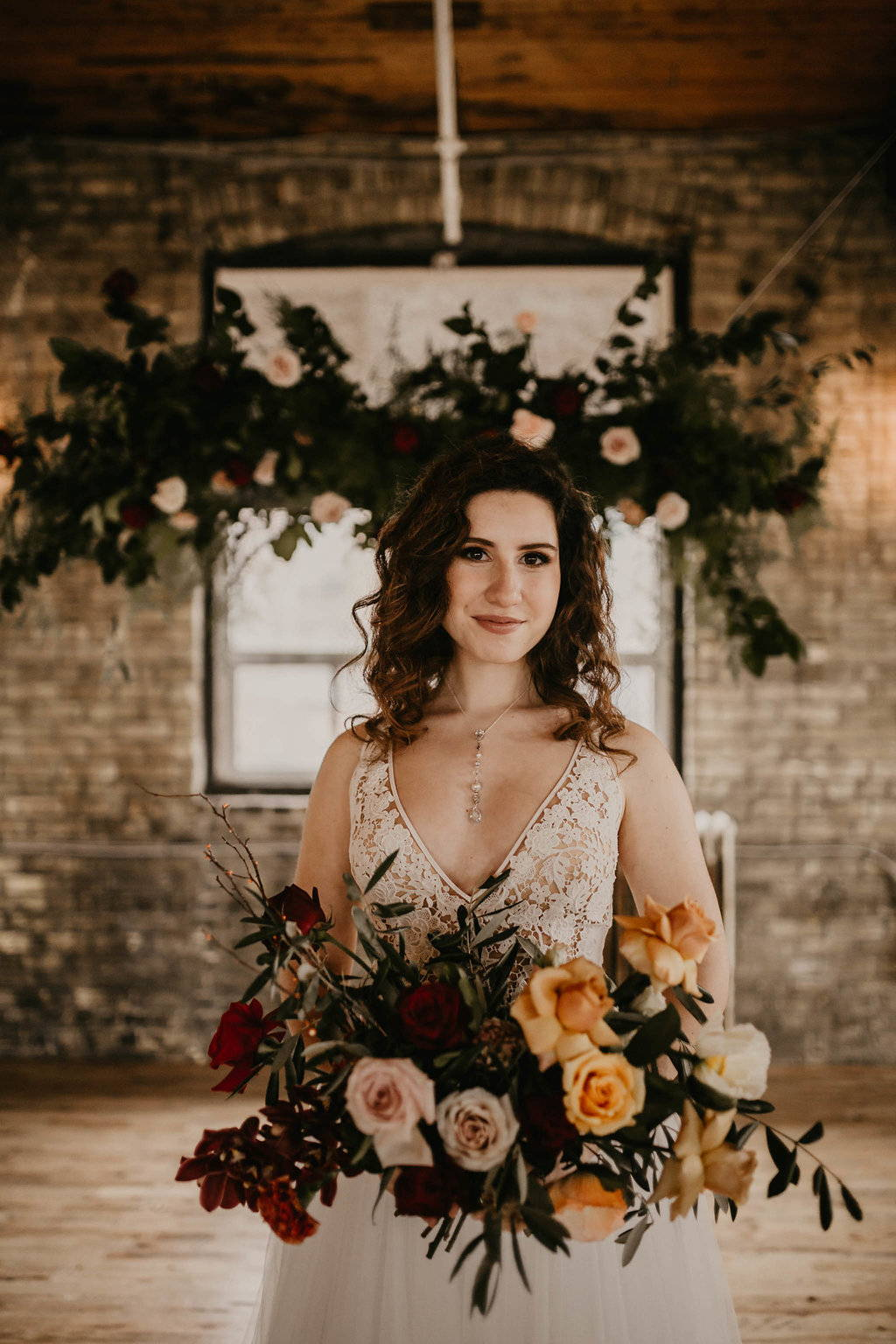 Bride standing in front of a floral installation with her bridal bouquet at The Jam Factory in Toronto