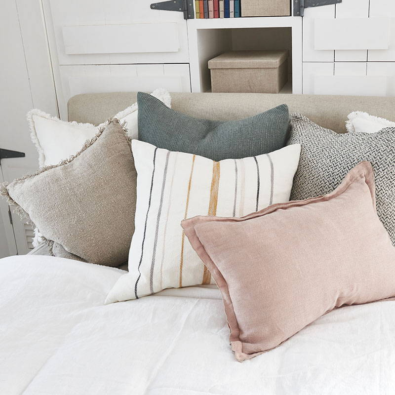 A mixture of linen cushions  on a bed