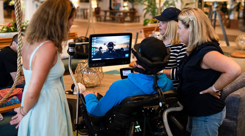 Junger Mann benutzt sein Gerät der I-Serie von Tobii Dynavox zum Kommunizieren