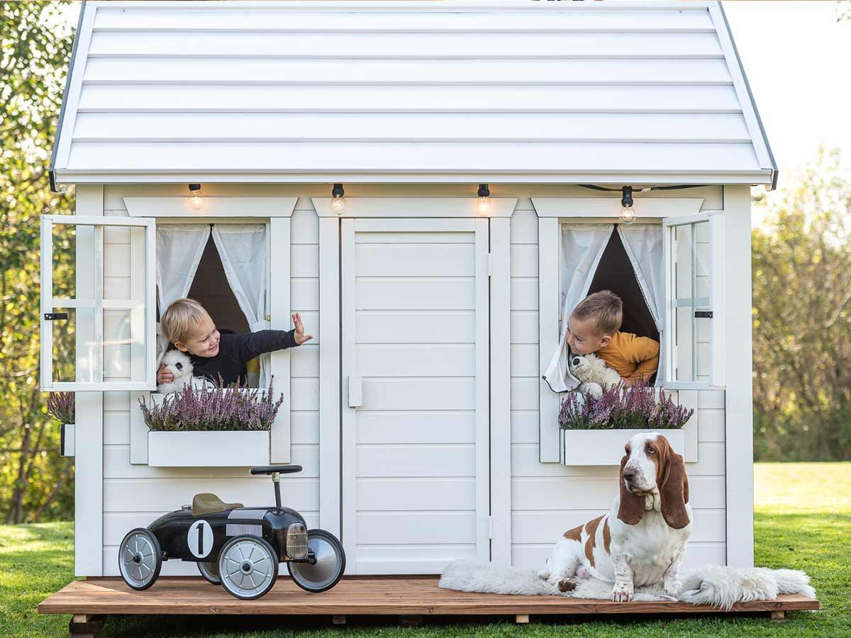 Wooden Playhouse in white color with two boys at the windows and a car and a big dog in front by WholeWoodPlayhouses