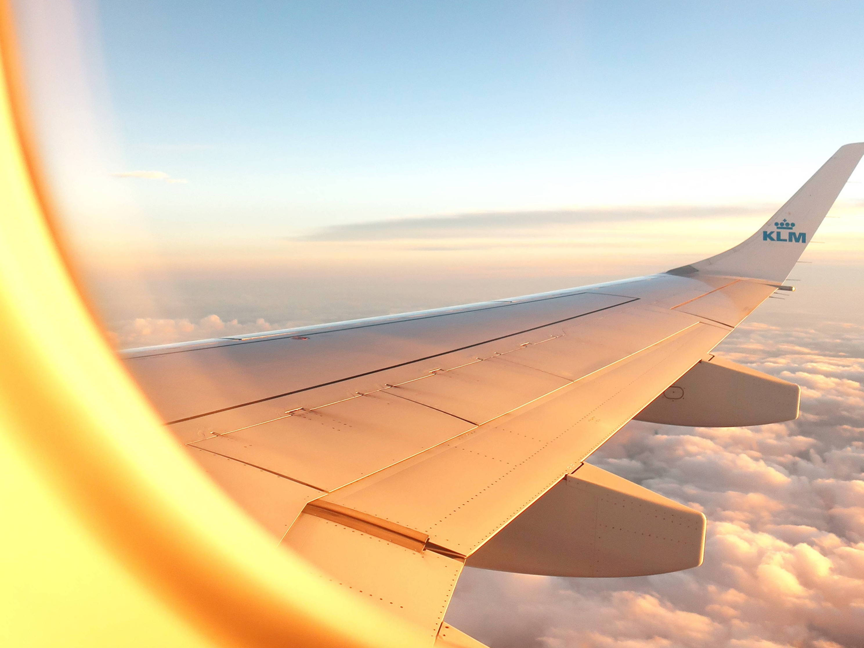 A view of the wing of an airplane through the window as it glides over white clouds