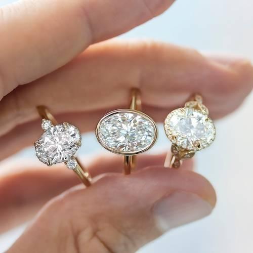three oval engagement rings - one bezel set