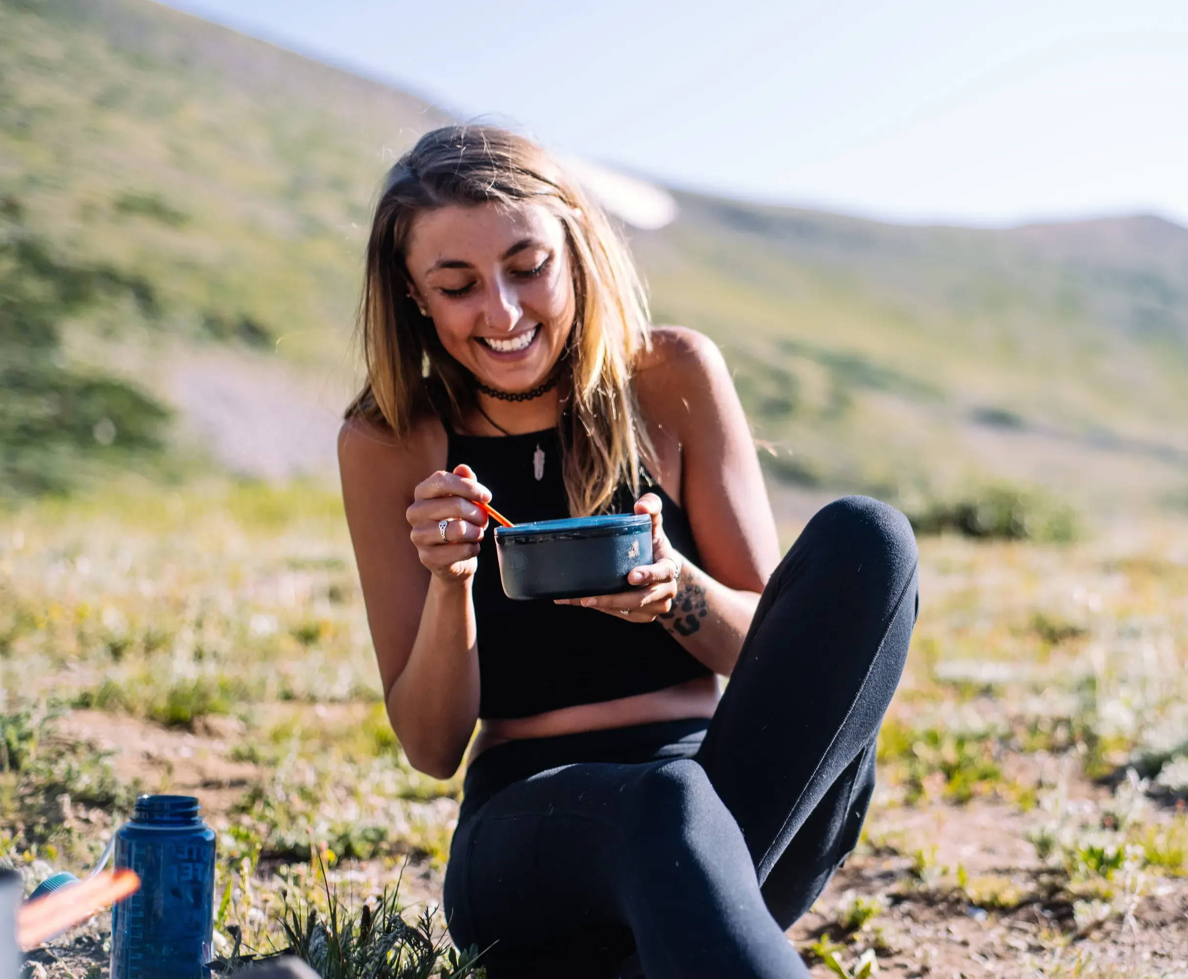 Woman eating soup in nature