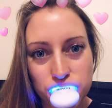 blonde girl using teeth whitening kit led light in mouth