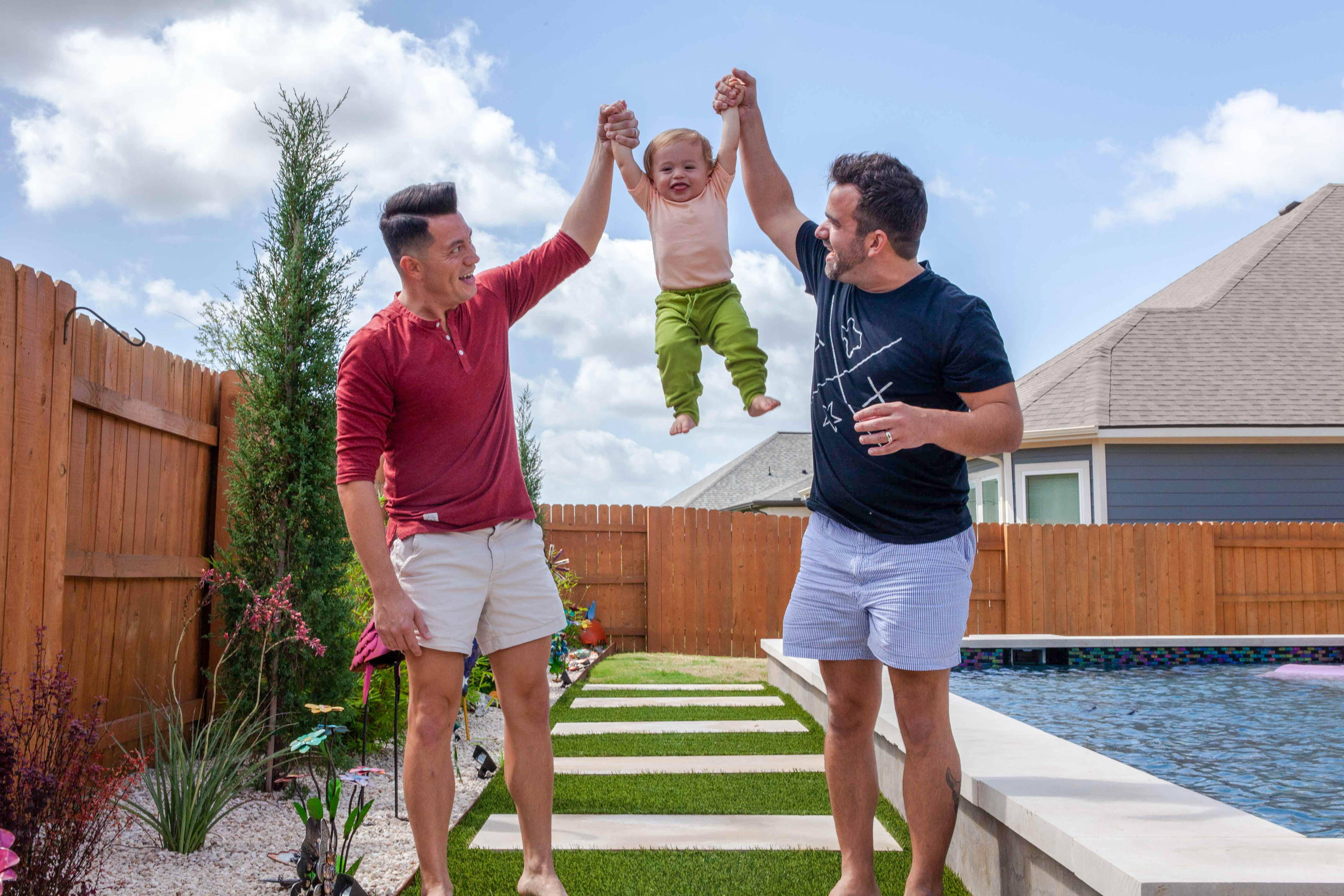 Image of Chris and Will DeGiglio-Wright  in outdoor/backyard area lifting son Riley in the air between them.