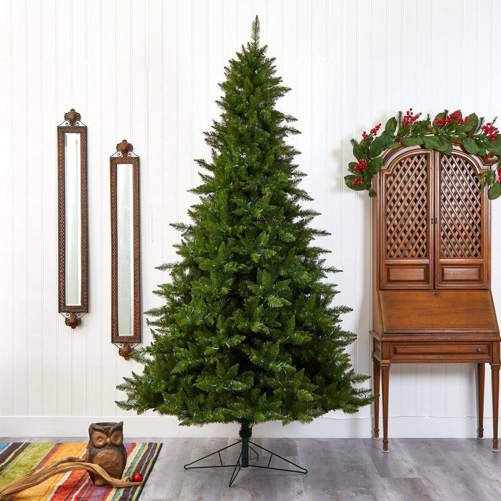 Nearly Natural's Vermont Spruce Artificial Christmas Tree decorated inside a living area next to a wooden cabinet