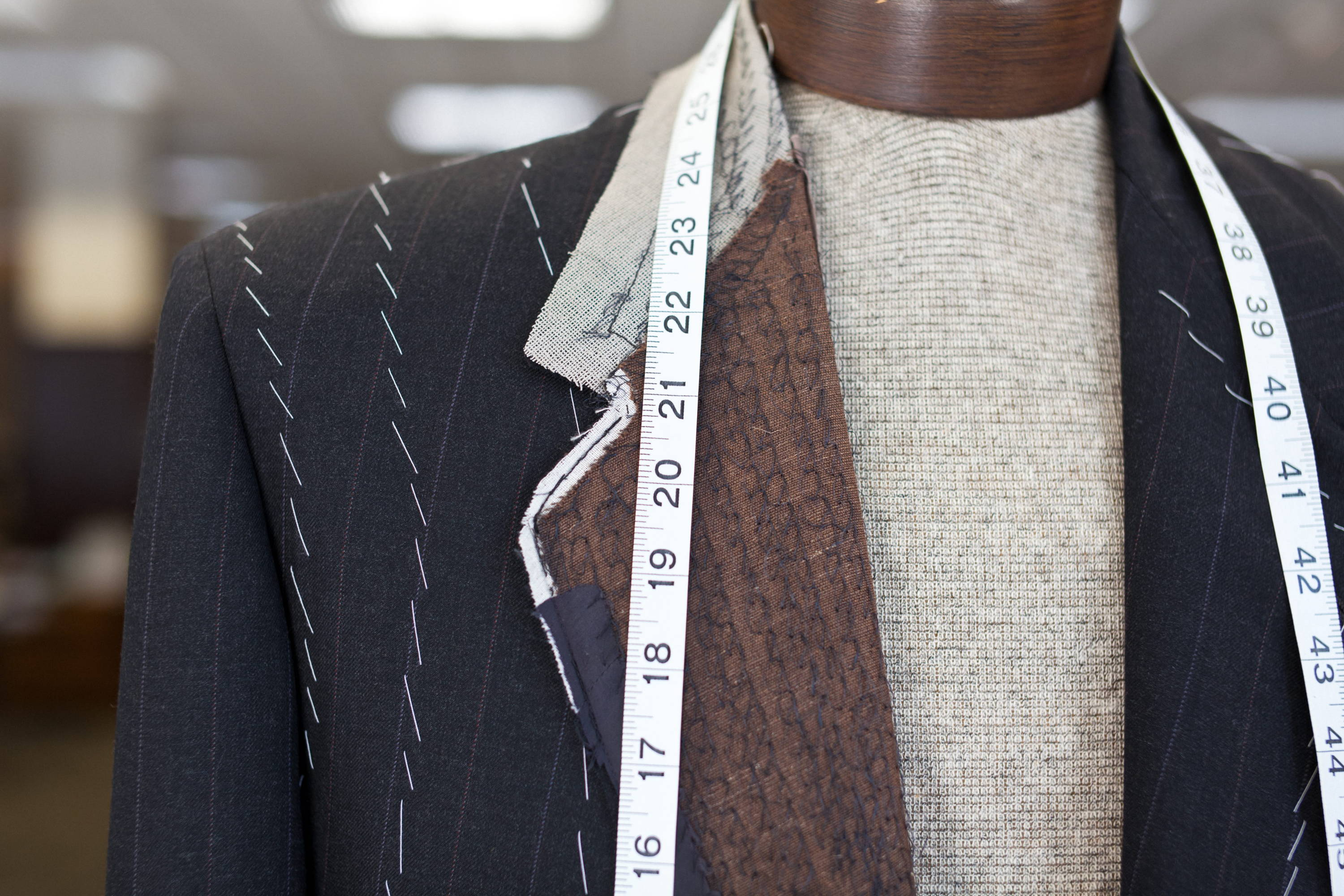 Tailored suit jacket mid-construction with pad stitching and basting
