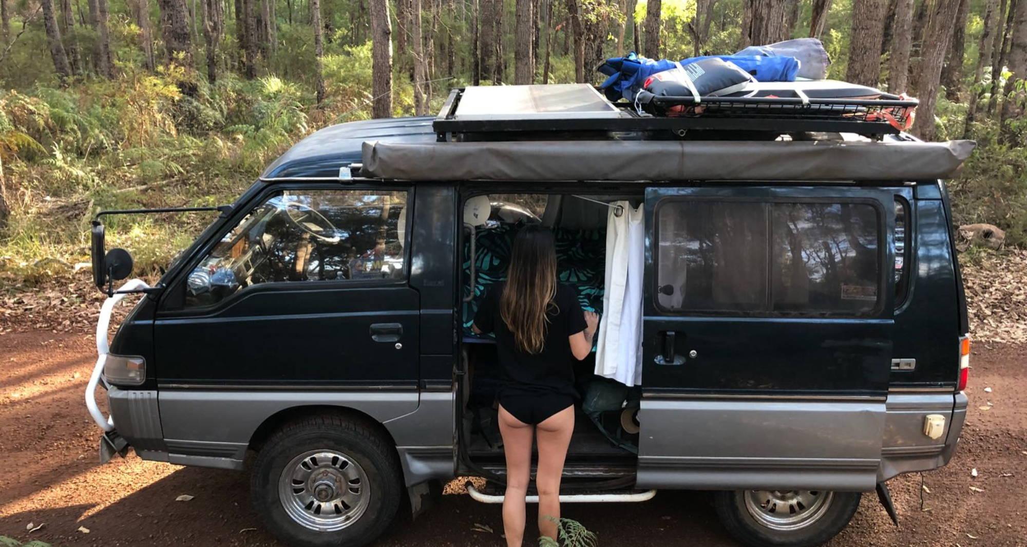 Woman standing in WAMA underwear packing camping essentials in her camper van.