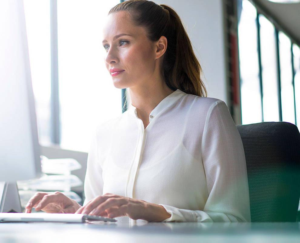 Frau im weißen Hemd, die auf ihren Computermonitor schaut.
