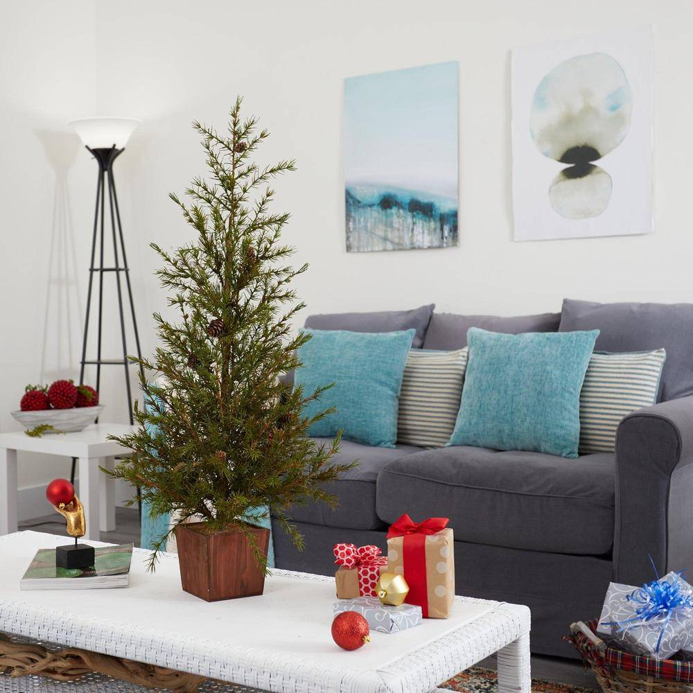 Artificial Christmas tree from Nearly Natural situated in a small apartment living room with Christmas presents on the table and a grey sofa