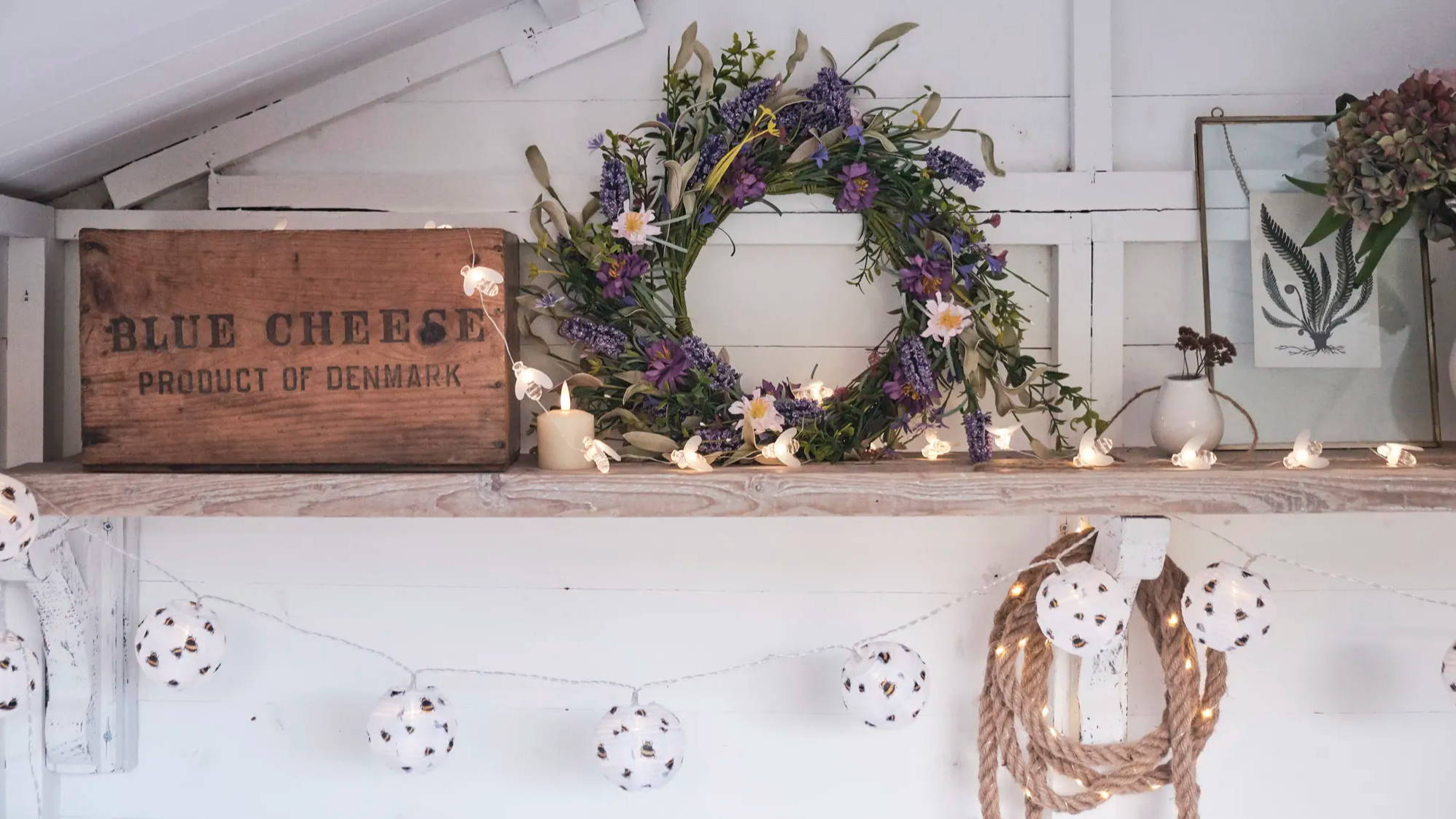Lavender wreath, bee fairy lights and bee lanterns displayed on shelf