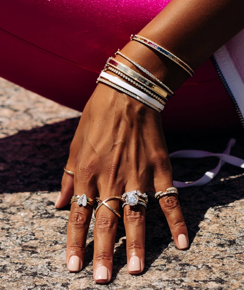 Close up of model wearing various Ring Concierge bangles and rings
