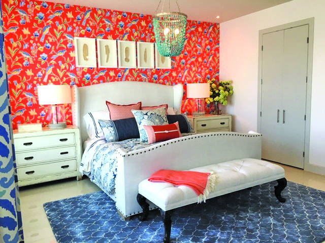 white bed in front of orange wall with a bird pattern, blue rug, white nightstand, white upholstered bench.