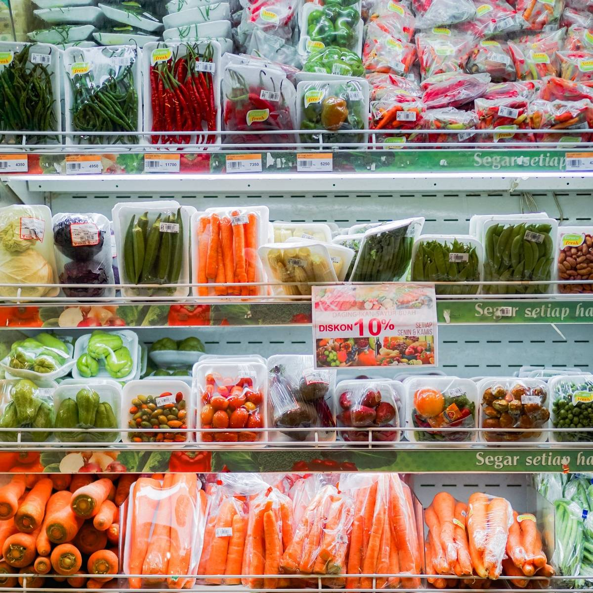 Shelves of vegetables wrapped in plastic packaging in a supermarket