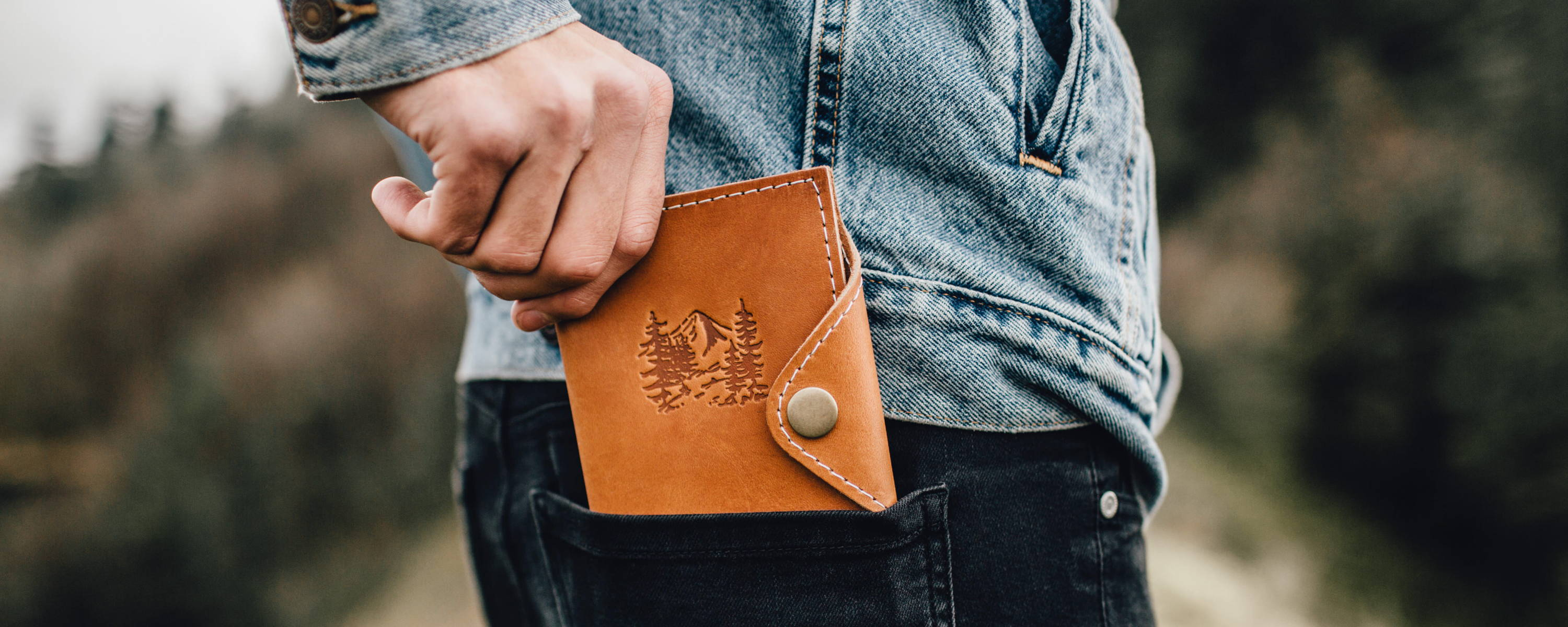 mans hand pulling leather snap journal out of his back pocket