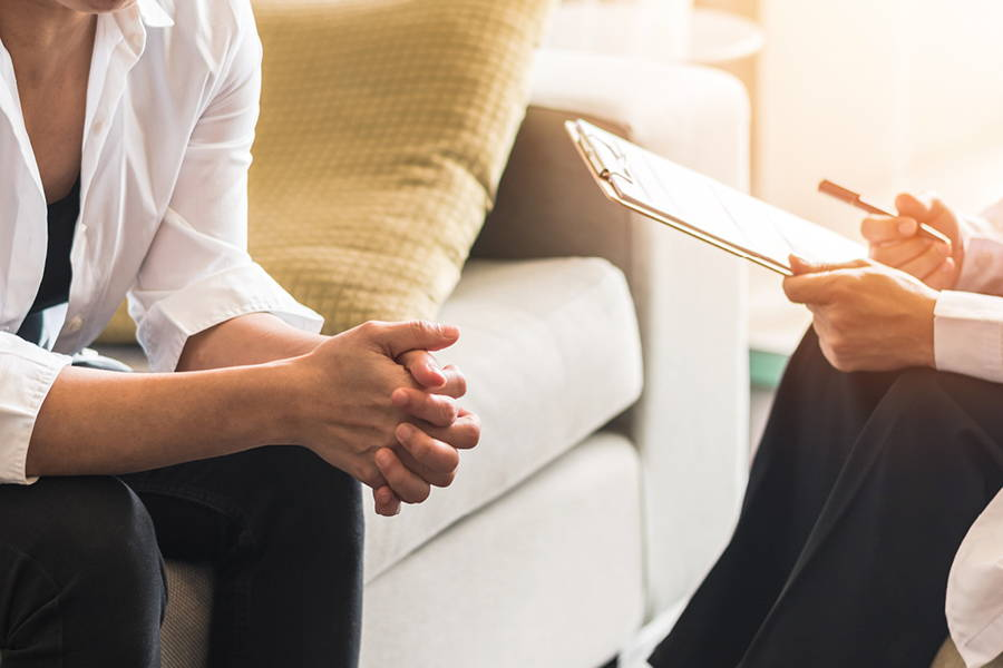 one person sitting on the couch while another person holds a pen and clipboard indicating an interview or consultation
