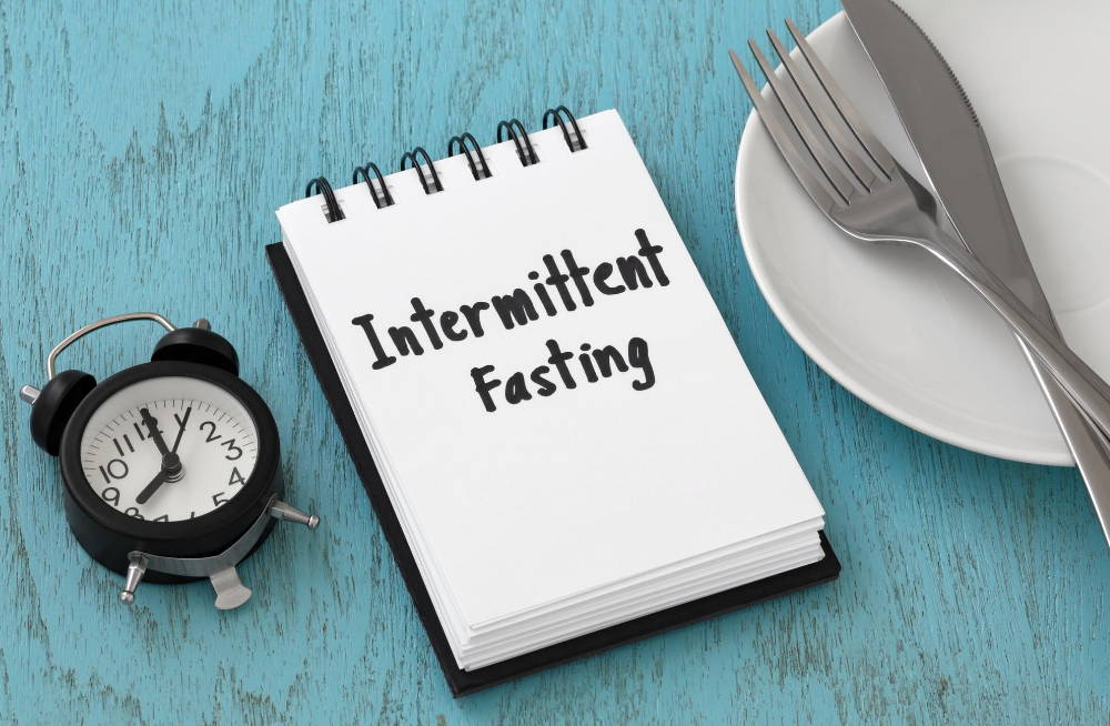 intermittent fasting word on notebook with clock fork knife on white plate|The Intermittent Fasting Guide For Optimal Health