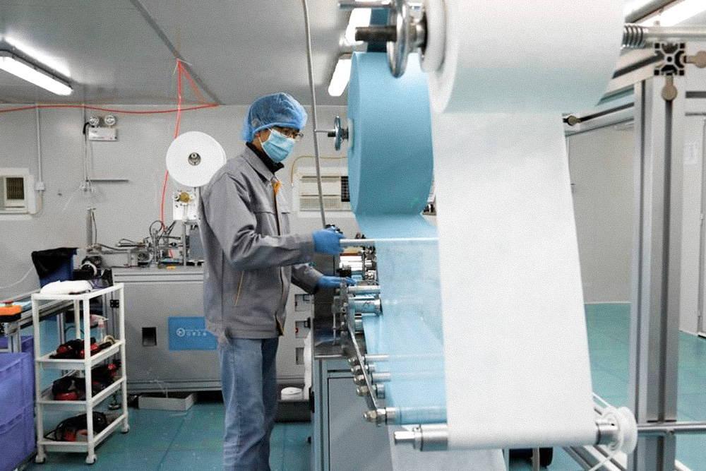 Trabajador de fabricación de mascarilla en sala blanca