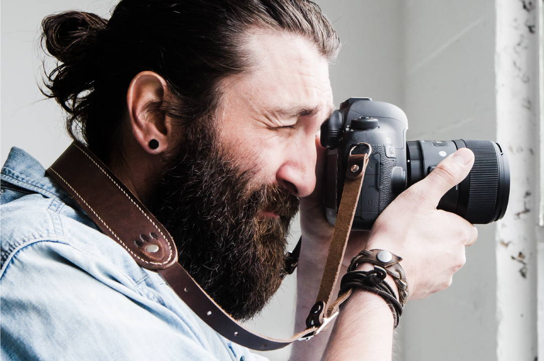 bearded man taking a photograph while using a leather camera strap