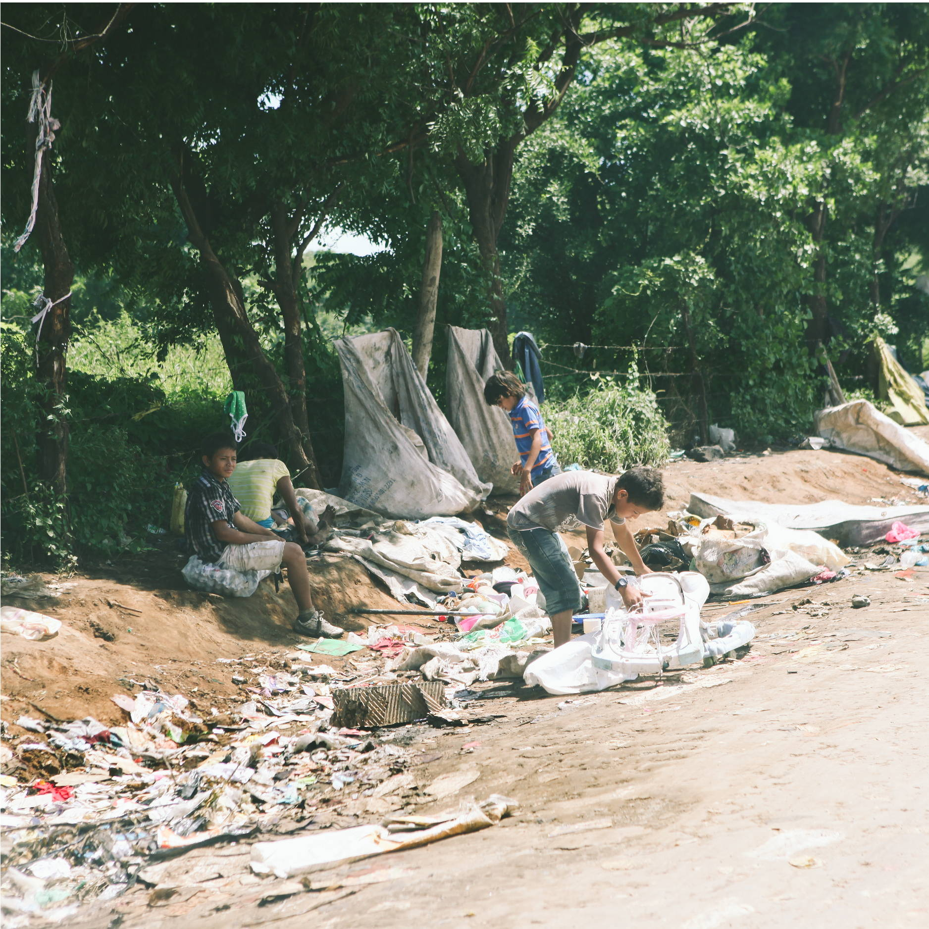 two young boys dig through trash that is strewn along the side of a nicaraguan dirt road as they look for food.