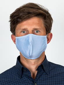 A man wearing a light blue face mask.