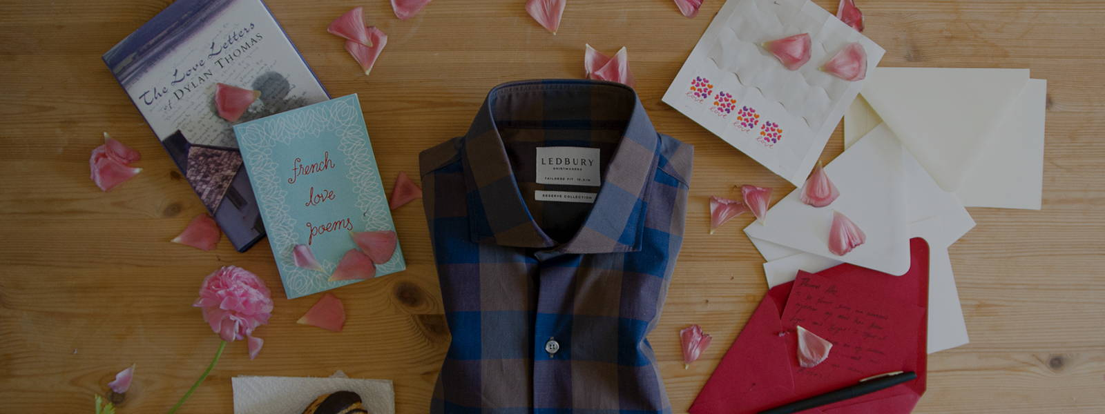 Featuring this weeks Sunday Shirting The Brown Tazewell Chambray Gingham Casual Shirt surround by flower pedals, a book, letters, stamps, coffee and pastries.