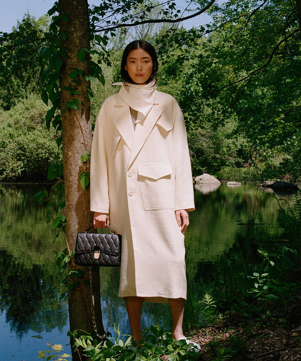 Resort 2020 campaign image. Model is wearing oversized white coat and a white leather bandana. She is holding a quilted black purse..