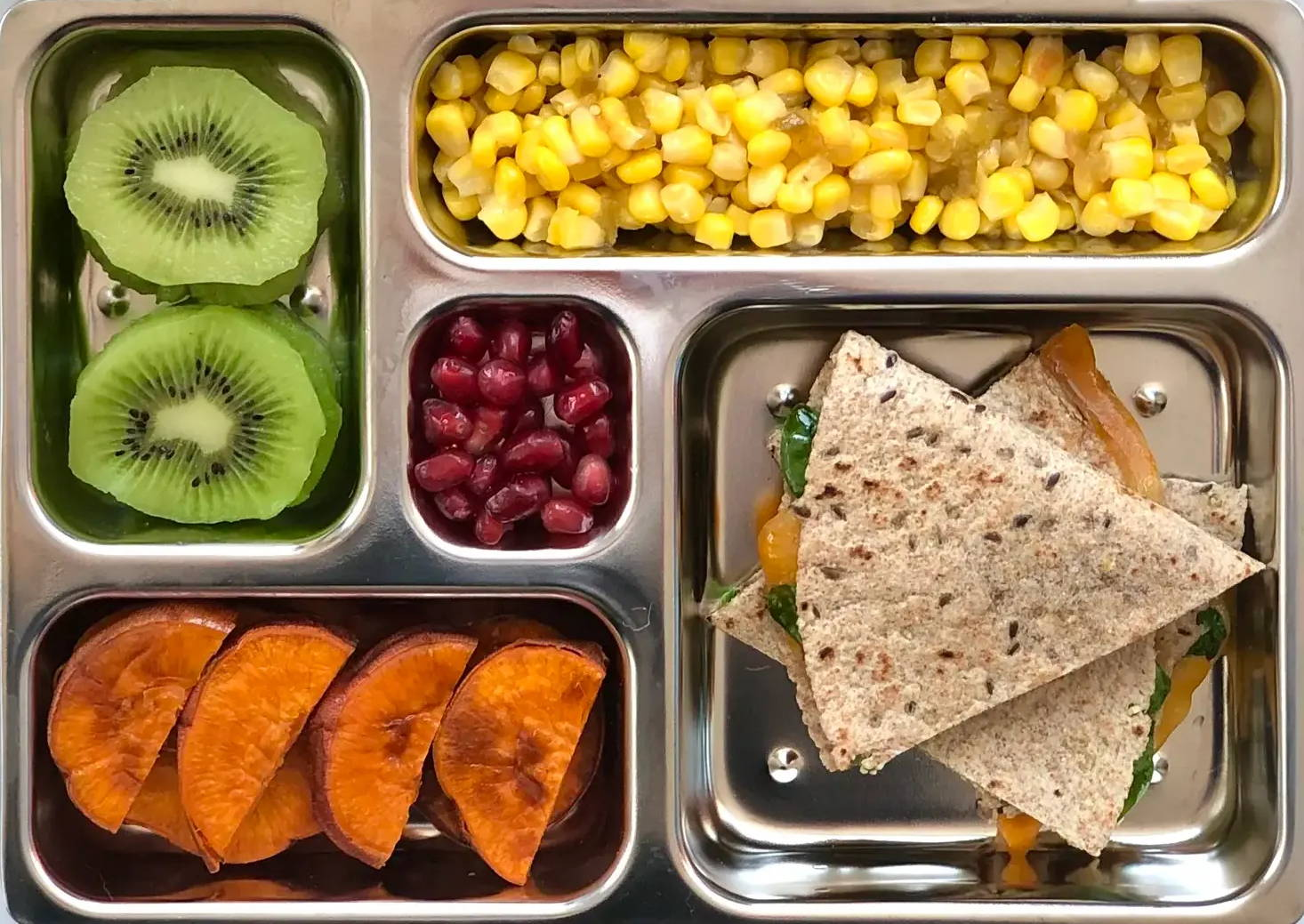 Sneak peek of a kid's quick and healthy school lunch containing  Spinach Cheese Quesadilla, Zippy Corn, Roasted Sweet Potato Rounds, Sliced Kiwi, and Pomegranate Seeds.