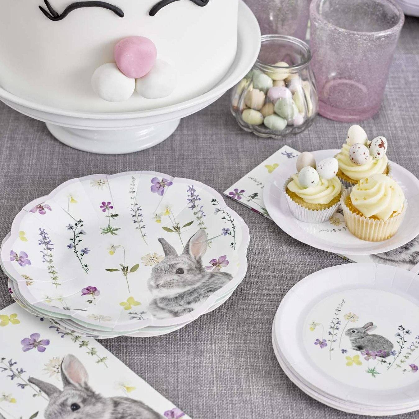 Easter party table set with Truly Bunny paper plates, Truly Bunny napkins and other Easter decorations and food.
