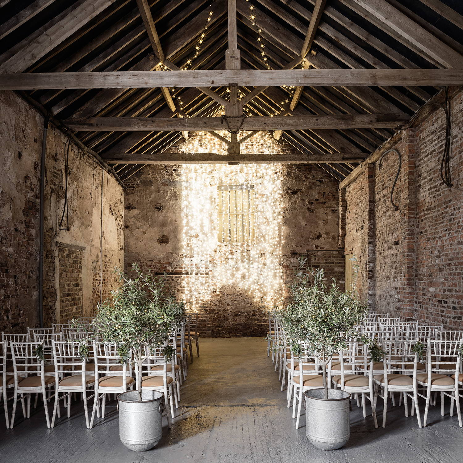 A barn wedding venue with a warm white fairy light backdrop