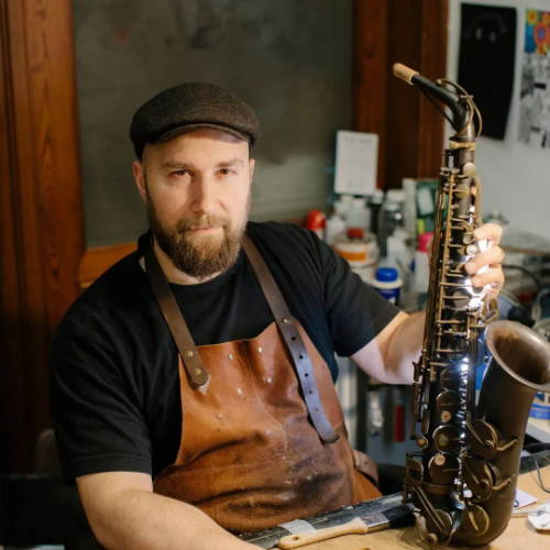 Karel Goetghebeur holding an Adolphe Sax brand  alto saxophone at the repair bench